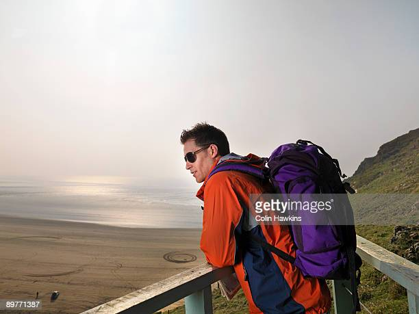 man hiking on cliff edge - colin hawkins stock pictures, royalty-free photos & images