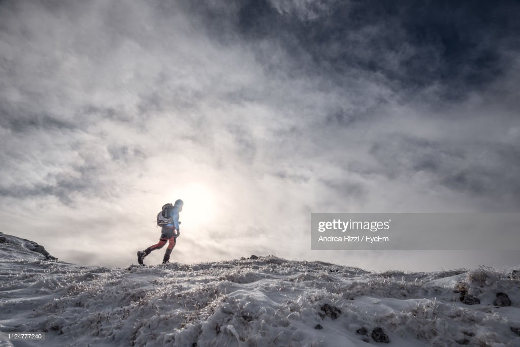 Man Hiking On Snowcapped Mountain Against Cloudy Sky : Foto stock