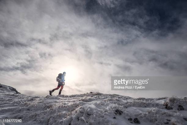 man hiking on snowcapped mountain against cloudy sky - andrea rizzi stockfoto's en -beelden