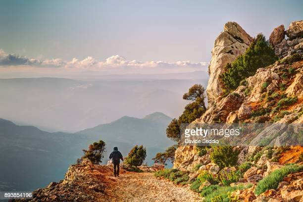 man hiking on the dirt road to the mountain 'punta corrasi' - sardinia stock pictures, royalty-free photos & images