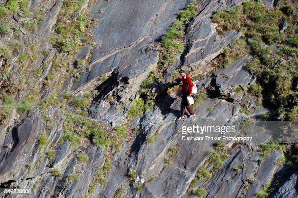 Man hiking on the rocky trail along a steep rocky incline.
