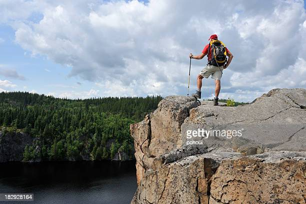 man hiking on top of high cliff, beautiful landscape - quebec stock pictures, royalty-free photos & images