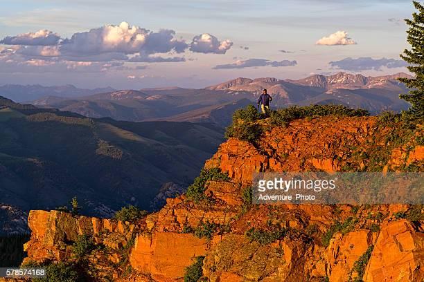 Man Hiking Scenic Mountain Canyon Rim at Sunset
