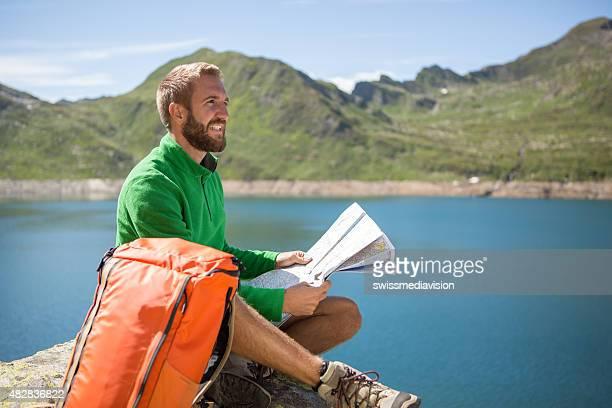 Mann sitzt auf dem Felsen wandern nach Wanderwege auf der Karte