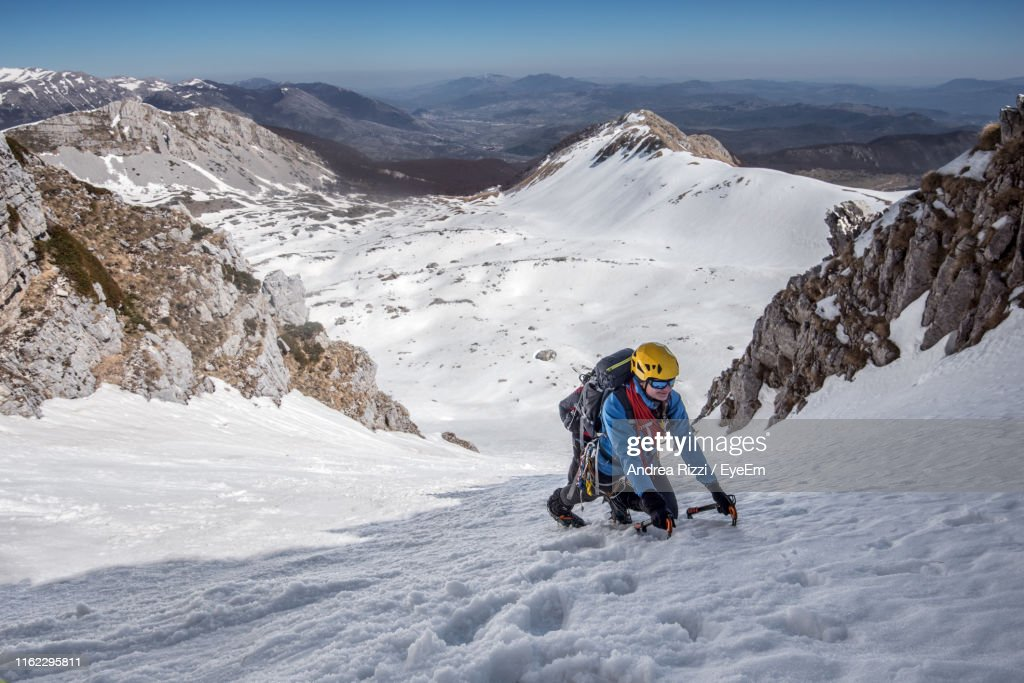 Man Hiking Snowcapped Mountain Against Sky : Foto stock