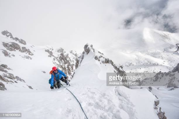 man hiking snowcapped mountain against sky - andrea rizzi fotografías e imágenes de stock