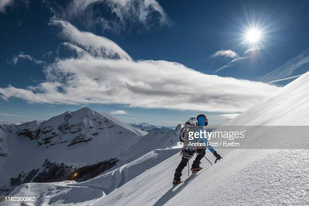 man hiking snowcapped mountain against sky - andrea rizzi stock pictures, royalty-free photos & images