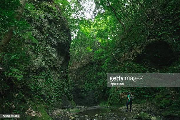 Man hiking through narrow and sheer walls of gorge, Japan