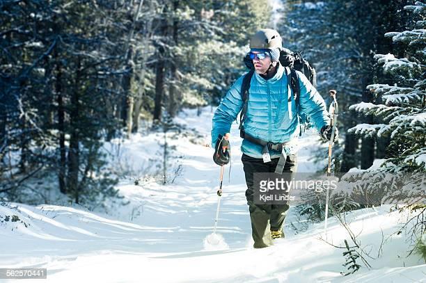 Man hiking through snowy forest