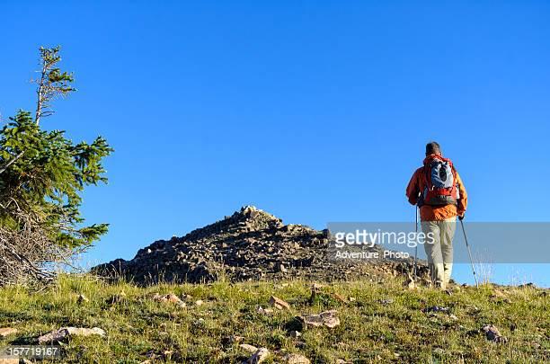man hiking toward mountain summit - gore range stock photos and pictures