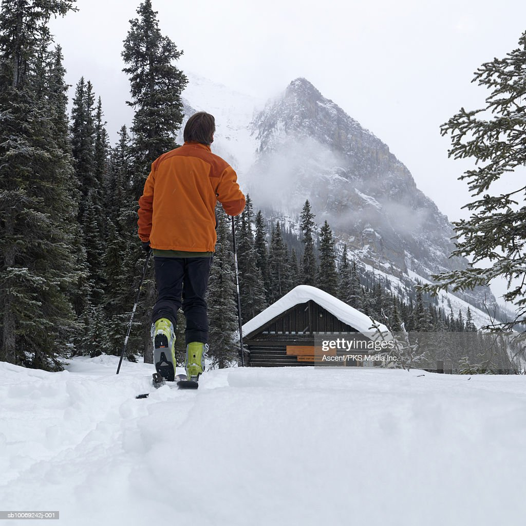 Man hiking towards hut, mountains in background, rear view : Stockfoto