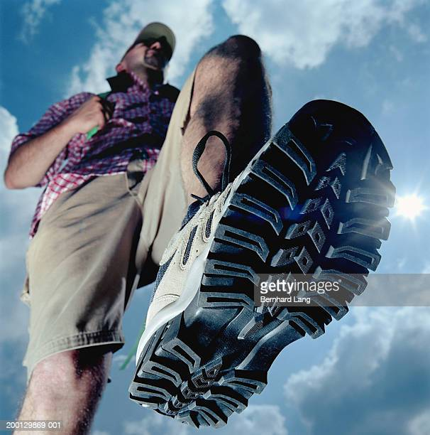 Man hiking under cloudy sky, view from below (focus on boot)