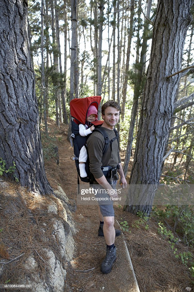 Man hiking with daughter (10-12 months) strapped to back in forest : Foto stock