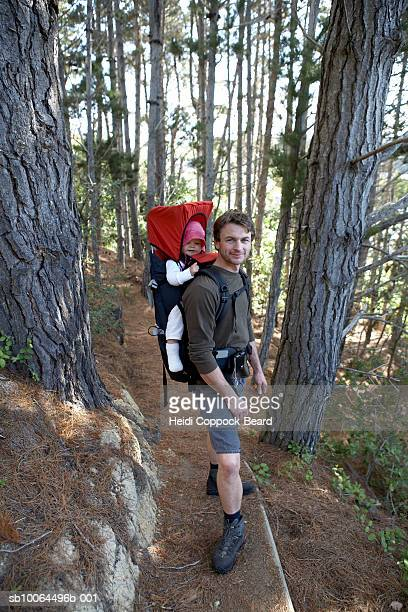 Man hiking with daughter (10-12 months) strapped to back in forest