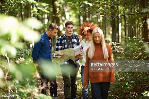 Man hiking with friends in forest holding map