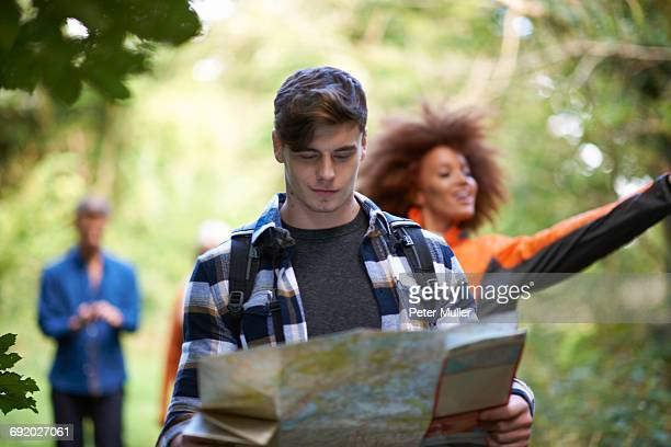 Man hiking with friends in forest looking at map