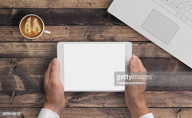 man hipster holding tablet knolling overhead view - wood table top stock photos and pictures