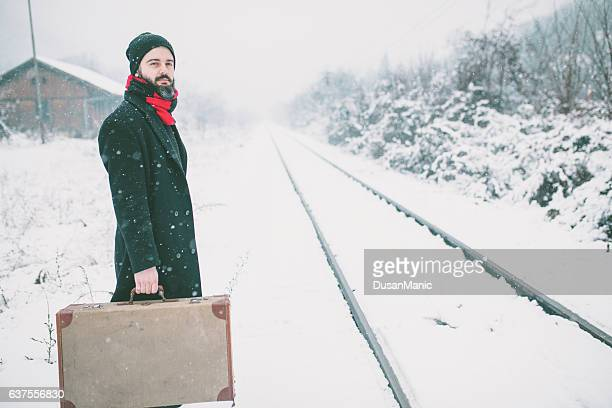 Man hipster with old vintage suitcase on railways
