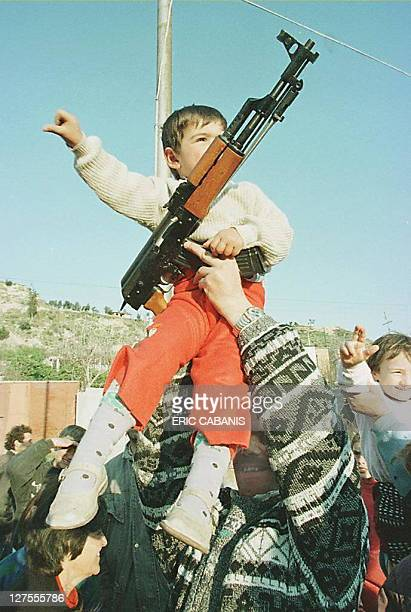 A man his son and a Kalashnikov assault rifle into the air in a sign of jubilation 09 March in Vlora after Albanian president Sali Berisha's...