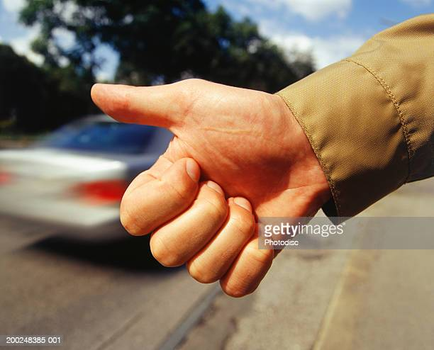 Man hitchhiking, Close-up of hand thumbing ride