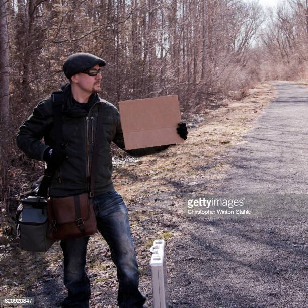 man hitchhiking with blank sign on rural road - christopher hitch stock pictures, royalty-free photos & images