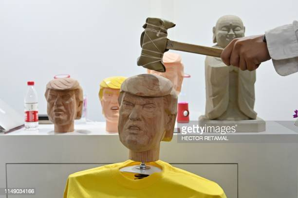 A man hits a bobble head in the likeness of US President Donald Trump as part of a stress relief station from a Japanese company during the Consumer...