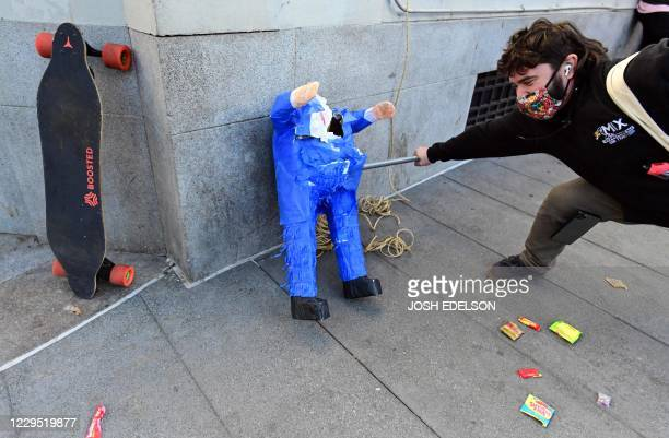 A man hits a Donald Trump pinata as people celebrate Joe Biden being elected President of the United States in the Castro district of San Francisco...