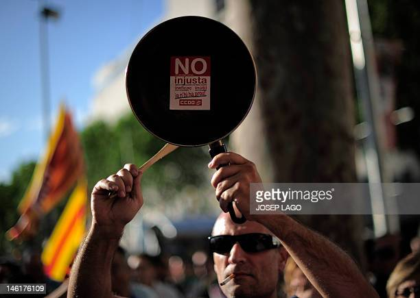 A man hits a frying pan during a protest against the request of financial support from the European Union by the Spanish government in front of a...