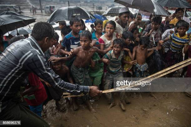 A man hits anxious Rohingya children with a cane as things get out of control during a humanitarian aid distribution while monsoon rains continue to...