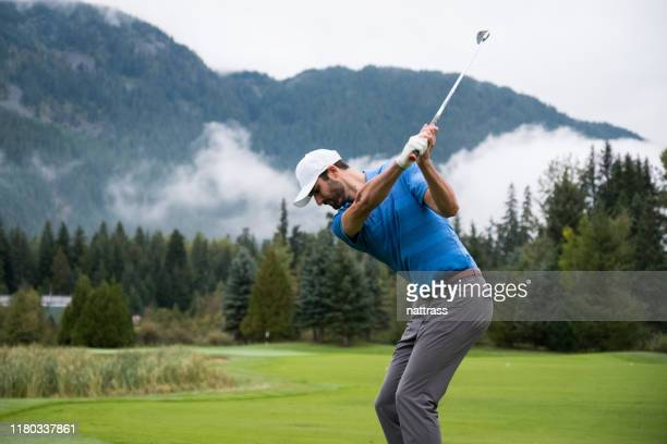 man hitting a golf shot towards the green - golfer stock pictures, royalty-free photos & images