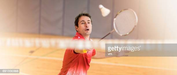 man hitting a shuttlecock with a badminton racket - badminton sport stock photos and pictures