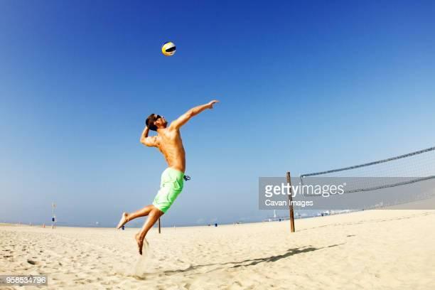 man hitting ball at beach against clear sky - strand volleyball der männer stock-fotos und bilder