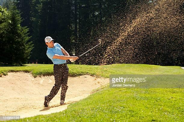 a man hitting out of a sand trap. - golf stock-fotos und bilder