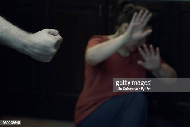 man hitting woman in darkroom - violence stock photos and pictures