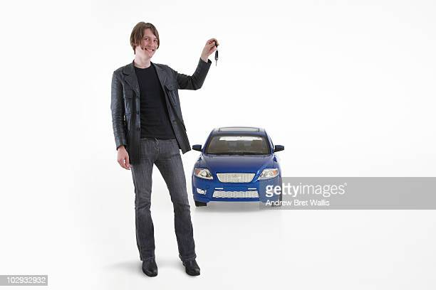 man hlding a car key in front of a toy car
