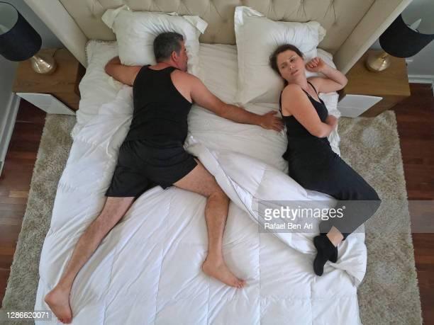 man hogging the bed in couple bedroom - rafael ben ari foto e immagini stock