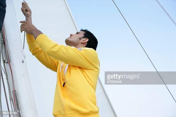 Man hoisting a sail