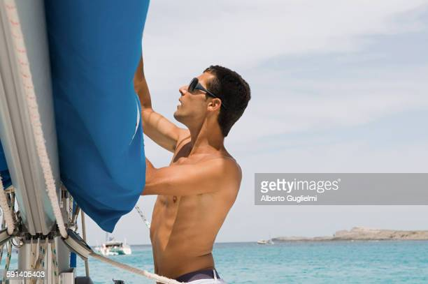 Man hoisting rigging on sailboat
