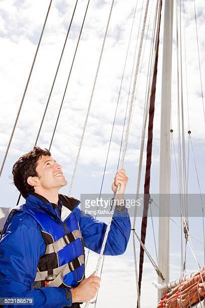 Homme hisser les voiles de bateau à voile
