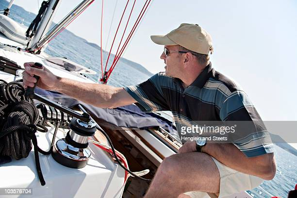 Man hoisting sail on yacht