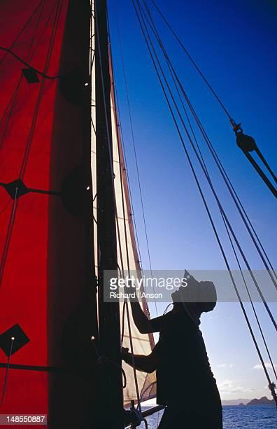 Man hoisting sails on yacht on Caribbean Sea  off St Barts.
