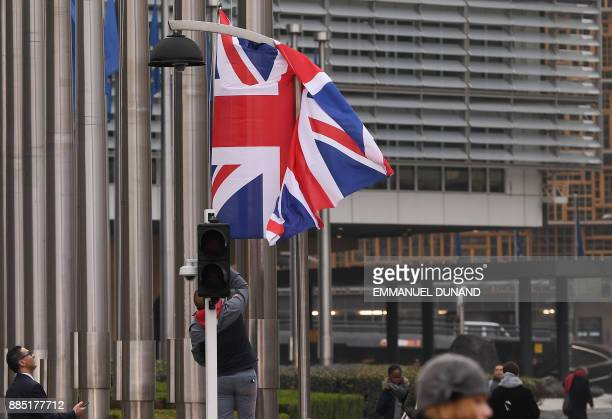 A man hoists a British flag in front of the European Union Commission on December 4 2017 in Brussels British Prime Minister Theresa May is set to...