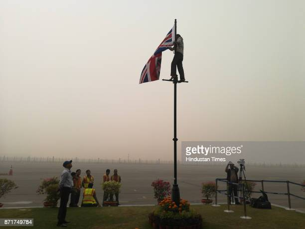 A man hoists British National Flag for Britain's Prince Charles and his wife Camilla Duchess of Cornwall who arrived at Air Force Station Palam today...