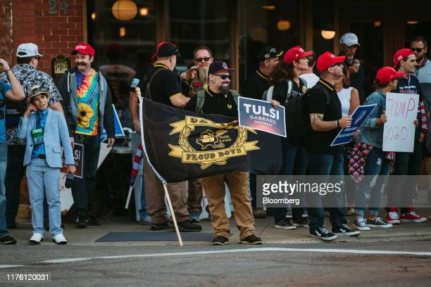 Man hold a Dayton Proud Boys flag and a sign for Representative Tulsi Gabbard, a Democrat from Hawaii and 2020 presidential candidate, ahead of the...