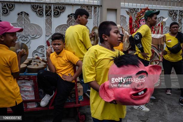 A man hold a mask of pig as they prepare during Grebeg Sudiro festival on February 3 2019 in Solo City Central Java Indonesia Grebeg Sudiro festival...