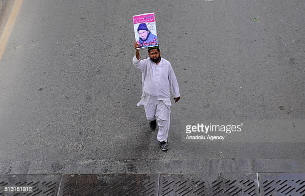 A man hold a portrait of Mumtaz Qadri former police bodyguard who shot dead Punjab's governor Salman Taseer in Islamabad in 2011 over his opposition...