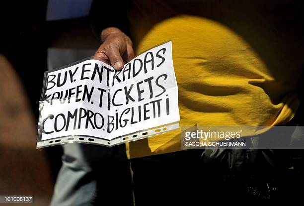 A man hold a sign which reads Buy tickets in front of Santiago Bernabeu stadium in Madrid on May 21 2010 ahead of the UEFA Champions League final...