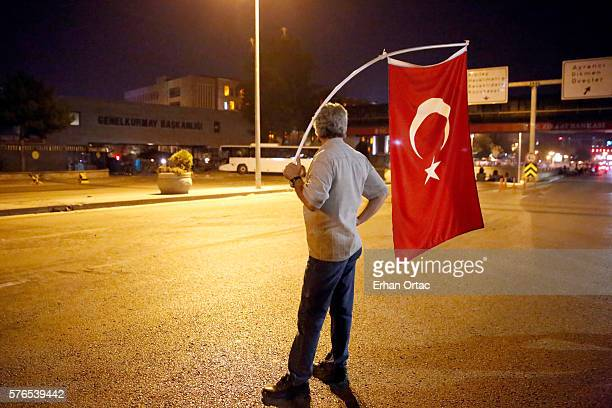 A man hold a Turkish flag stand in front of the Turkish Army's Headquarters on the main street of Ankara July 16 Turkey Istanbul's bridges across the...