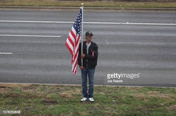 A man hold a US Flag as the train carrying former President George HW Bush to his final resting place passes by on December 6 2018 in Texas President...