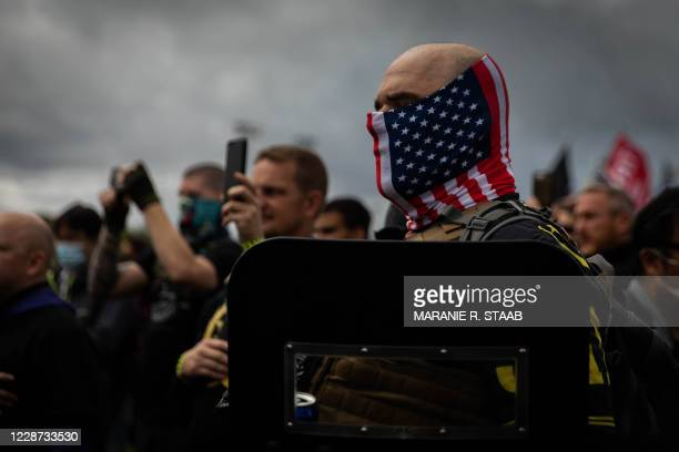 Man hold his hand to his heart as a Proud Boys organizer recites the Pledge of Allegiance during a Proud Boys rally at Delta Park in Portland, Oregon...